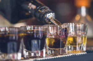 close-up of drinks being poured at a bar