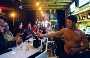 shirtless male bartender pouring a drink