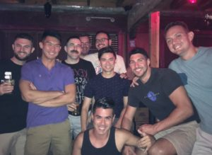 group of men smiling in a bar