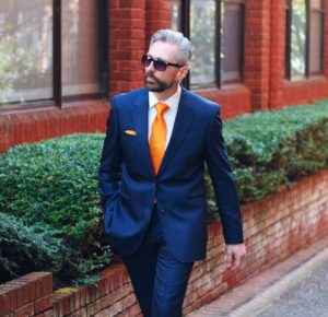 man walking down street in bright orange tie